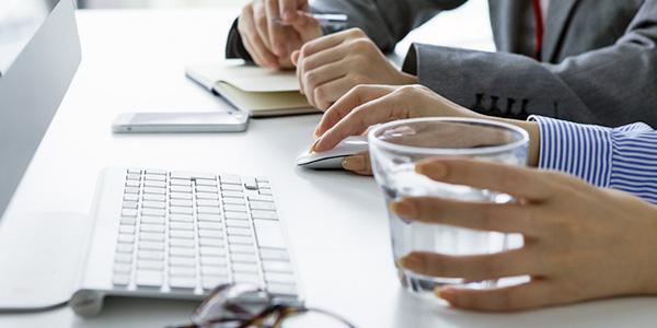 会社内で机に置いた水の入ったコップを手に取る社員の手